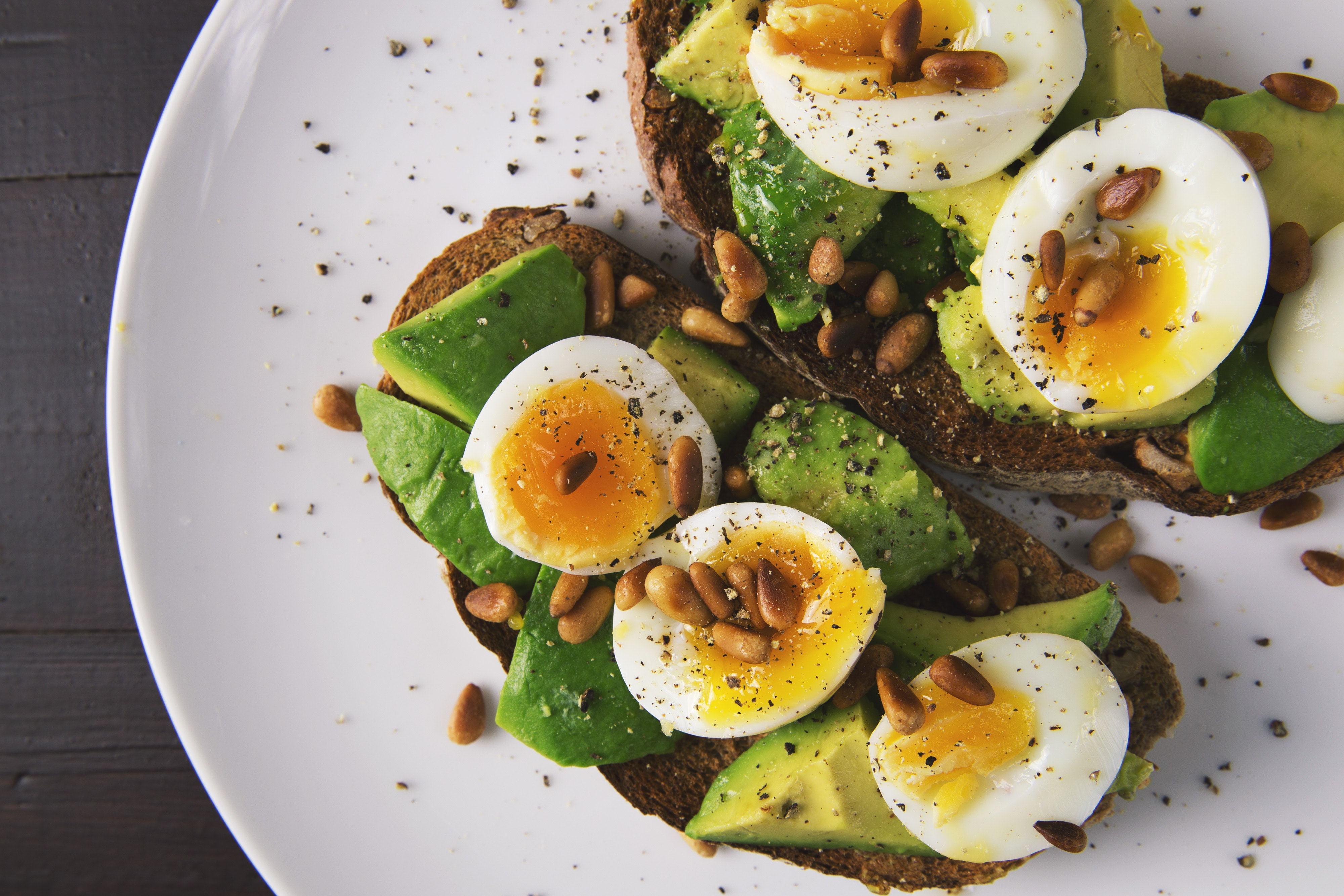 Avocado toast with egg and pine nuts