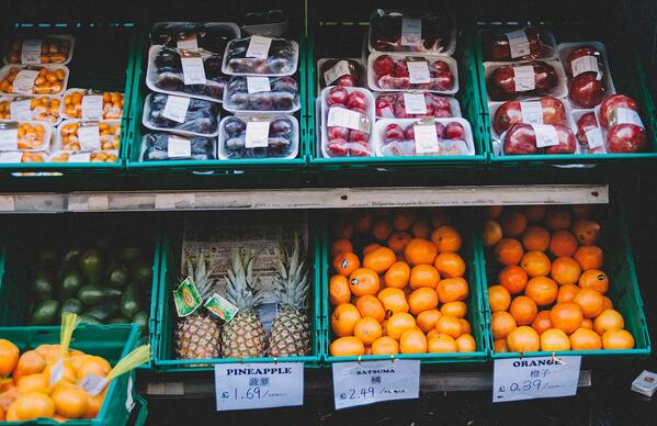 Outdoor market stall with fresh pineapple, oranges and packaged stone fruit