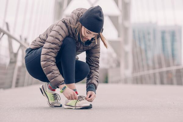 Woman in sneakers, workout clothes and a jacket lacing up her shoes for some exercise
