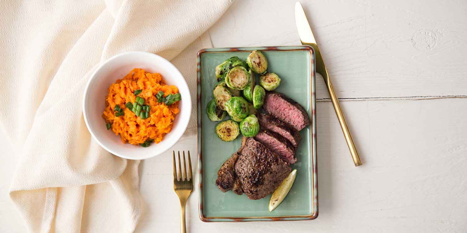 Plate of lean steak, sweet potato and brussel sprouts