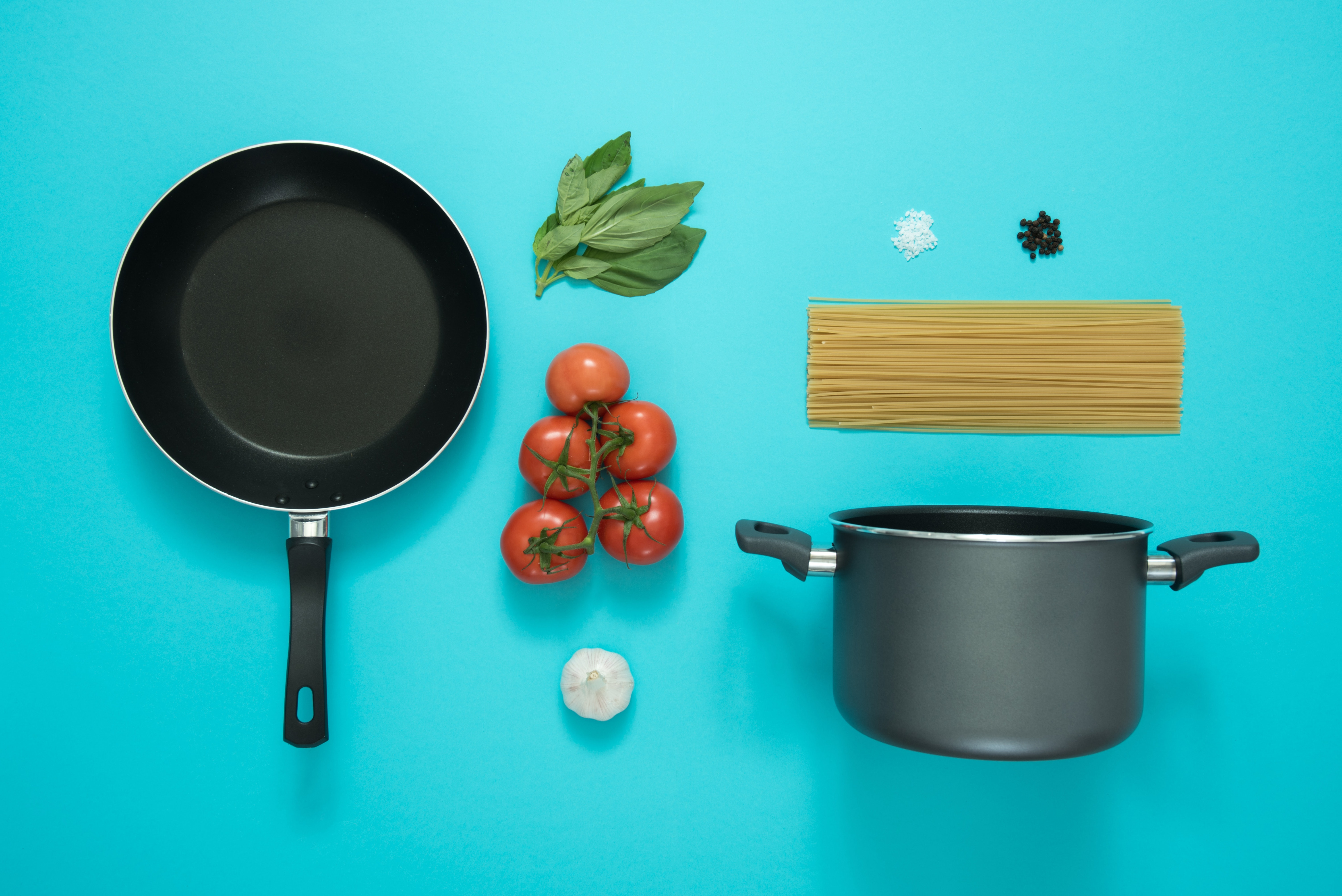 Home cooking station with a frying pan, pot, pasta, fresh herbs and tomato