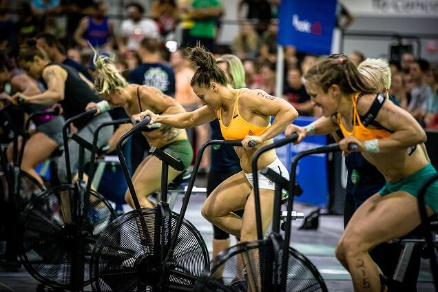 Female CrossFit athletes competing on the assault bike
