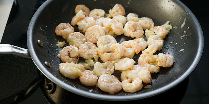 Shrimp added to previously sauteed garlic in a non-stick pan on an electric stovetop