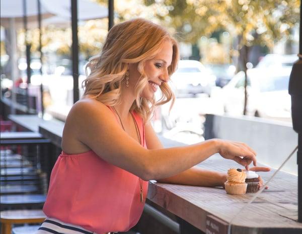 girl smiling at cupcake