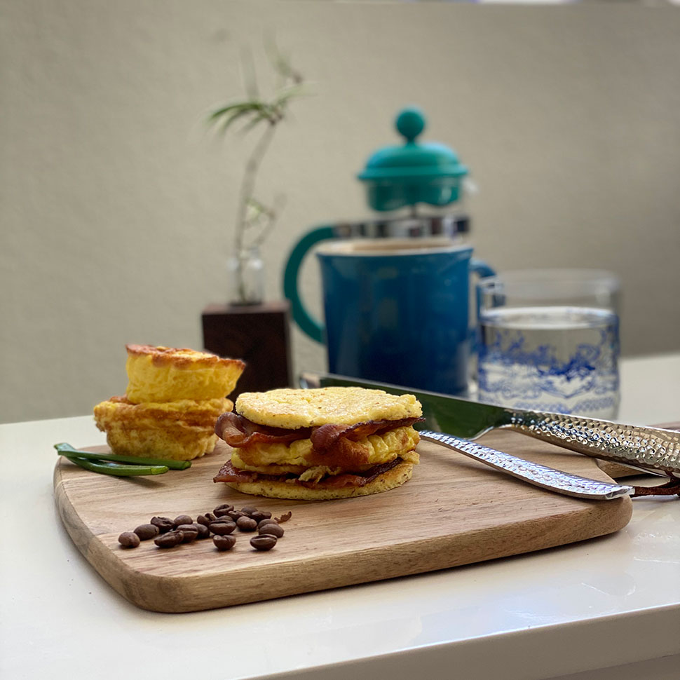 keto-breakfast-sandwich-placed-on-a-brown-wooden-board-with-a-mug