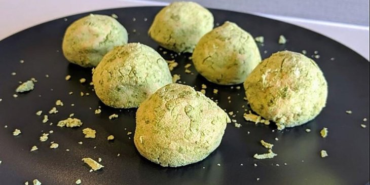 Green tea matcha fat bombs plated on a circular black plate