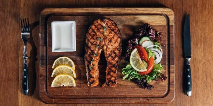 Paleo dish of grilled fish filet with a simple side salad plated on an oak cutting board