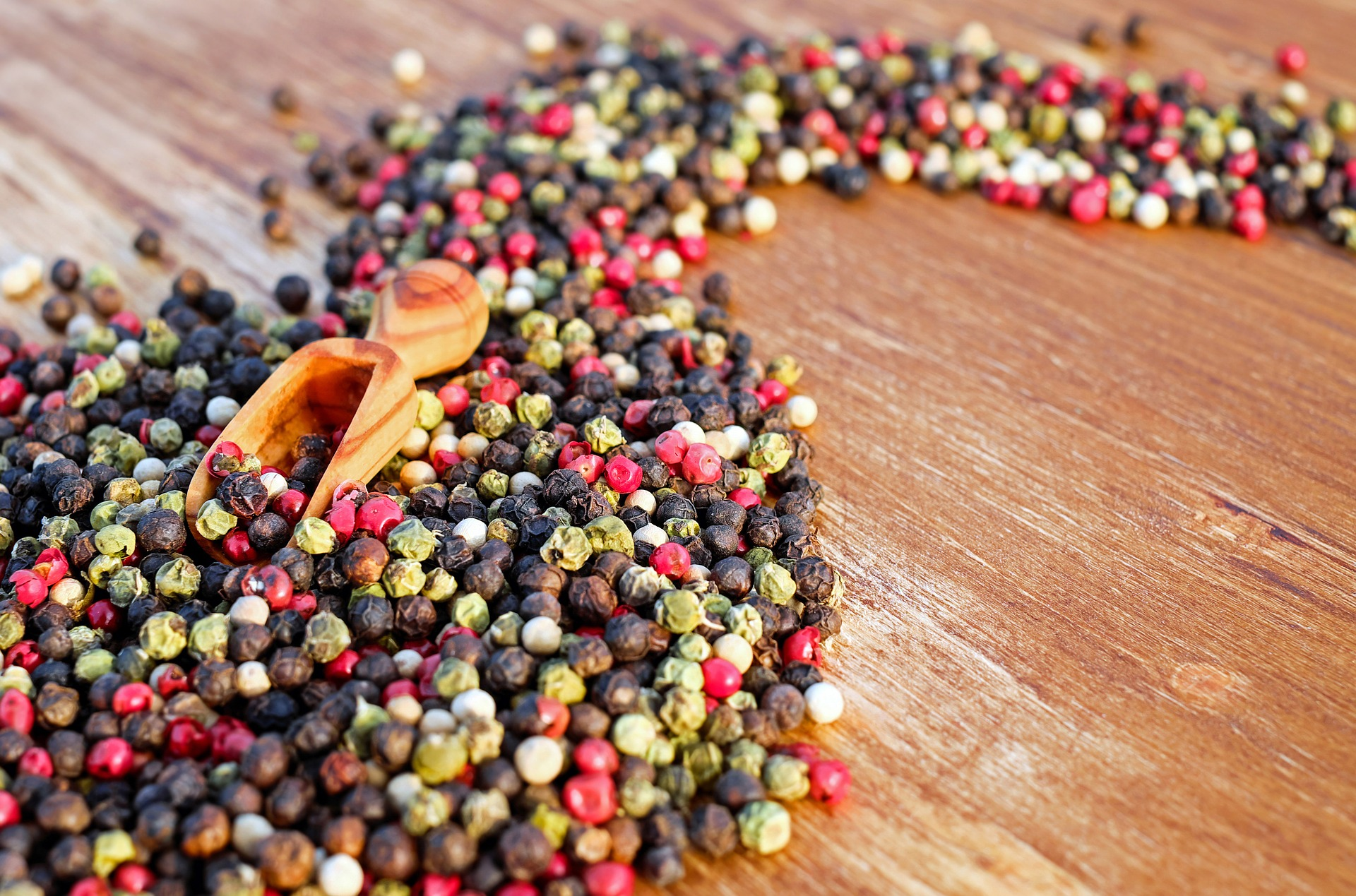 Black, red, green and white peppercorns in a curved pattern on a table top