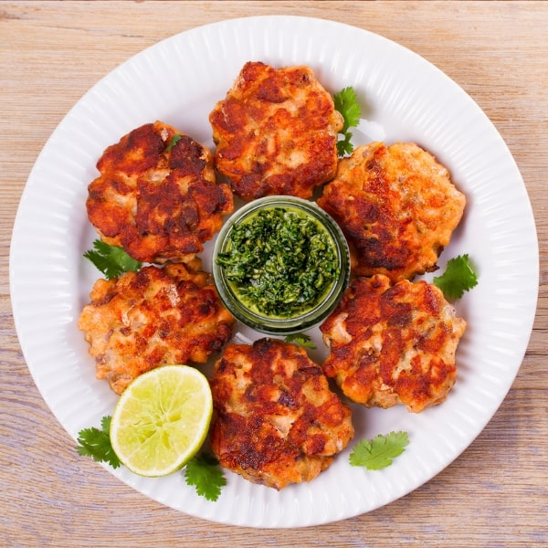 low-carb-keto-baked-salmon-cakes-recipe-chimichurri-sauce-plated-on-a-white-plate