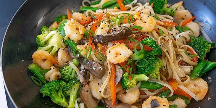 cooking shrimp noodle stir fry in wok for meal prep