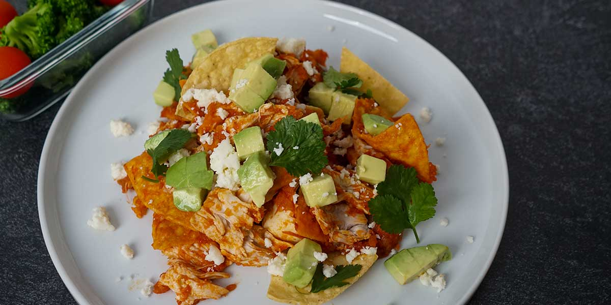 Chilaquiles Chicken Recipe plated on a beautiful white porcelain plate on a black mate background