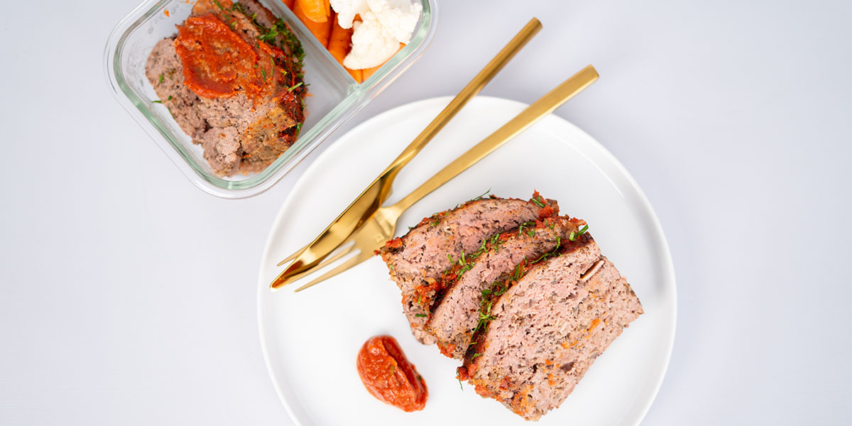 Gluten-Free Paleo Meatloaf Recipe on a White Plate with Golden Utensils and a Meal Prep Container