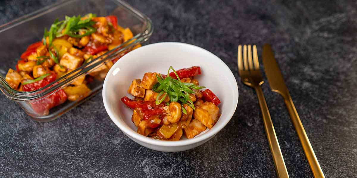 Paleo Cashew Chicken Recipe served on a white bowl and a meal prep container with golden silverware placed on a black background