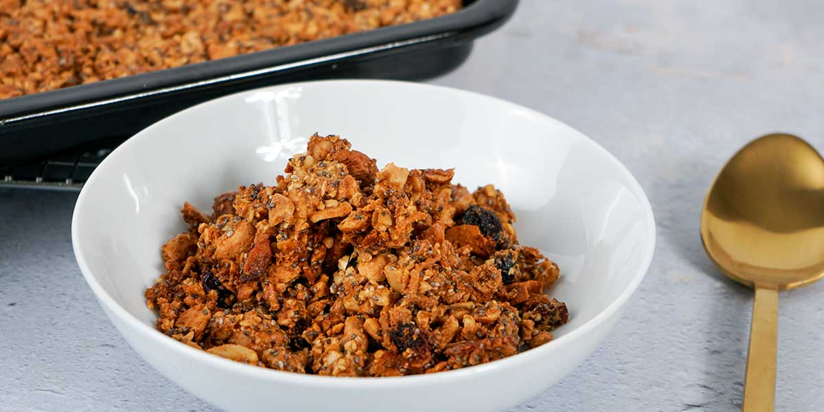 Paleo Gluten Free Granola Recipe served on a white bowl with a black tray in the background