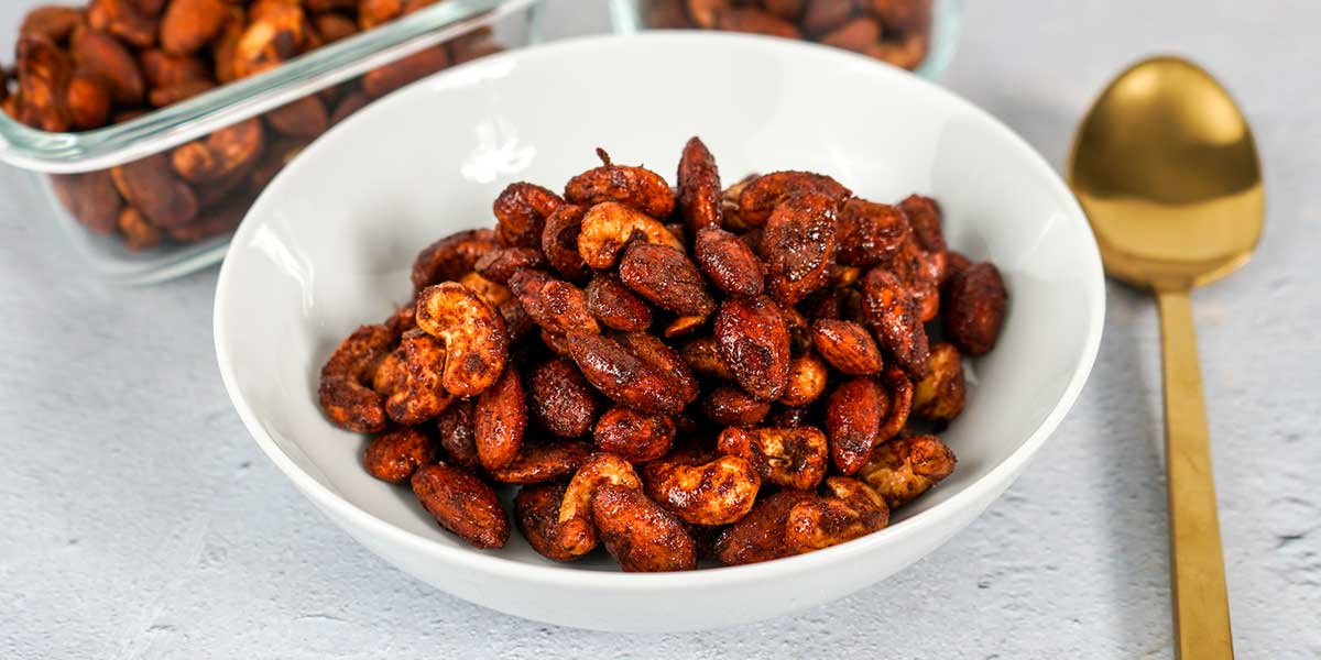 Paleo Roasted Spiced Nuts Recipe plated on a white bowl and also on meal prep containers in the background
