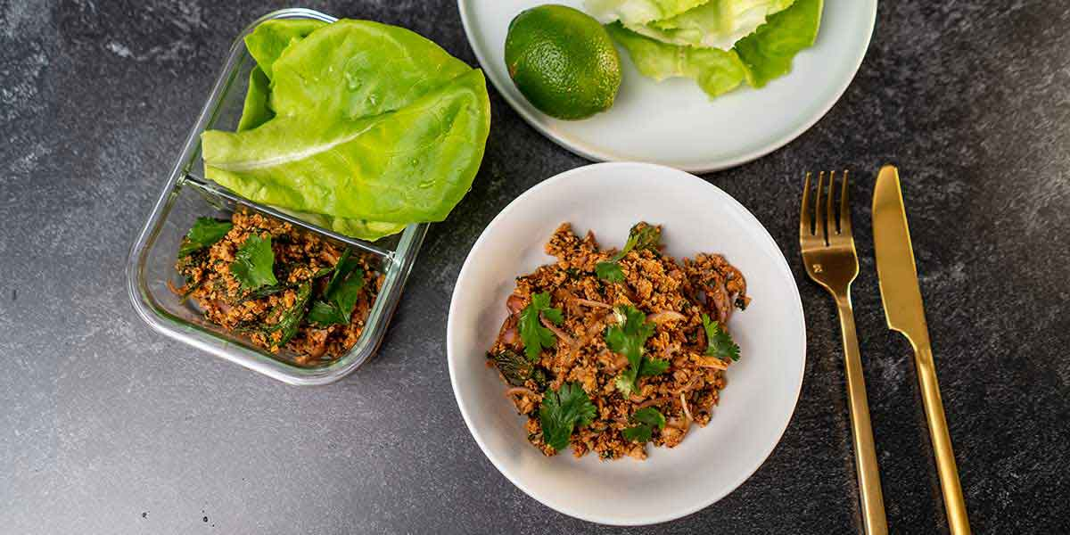Paleo Thai Turkey Larb Recipe served on white plates with golden silverware and a meal prep container on the side