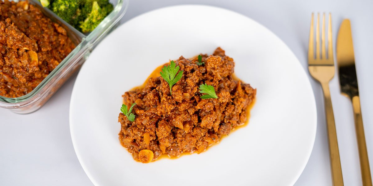 Paleo-beef-sloppy-joe-on-a-white-plate-with-parsley-garnish