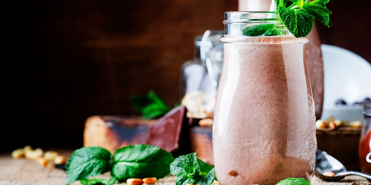 Peanut Butter-Chocolate Keto Breakfast Shake Recipe with basi mint in a wooden background