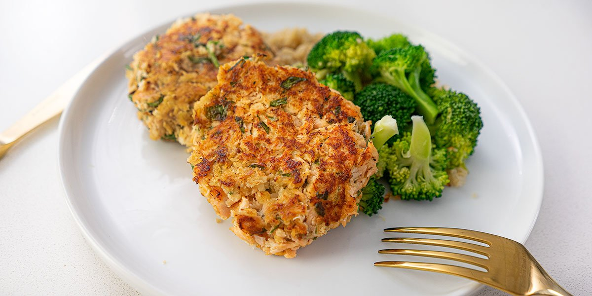 The Best Salmon Cakes Recipe Ever plated on a white round plate next to bright broccoli and golden silverware
