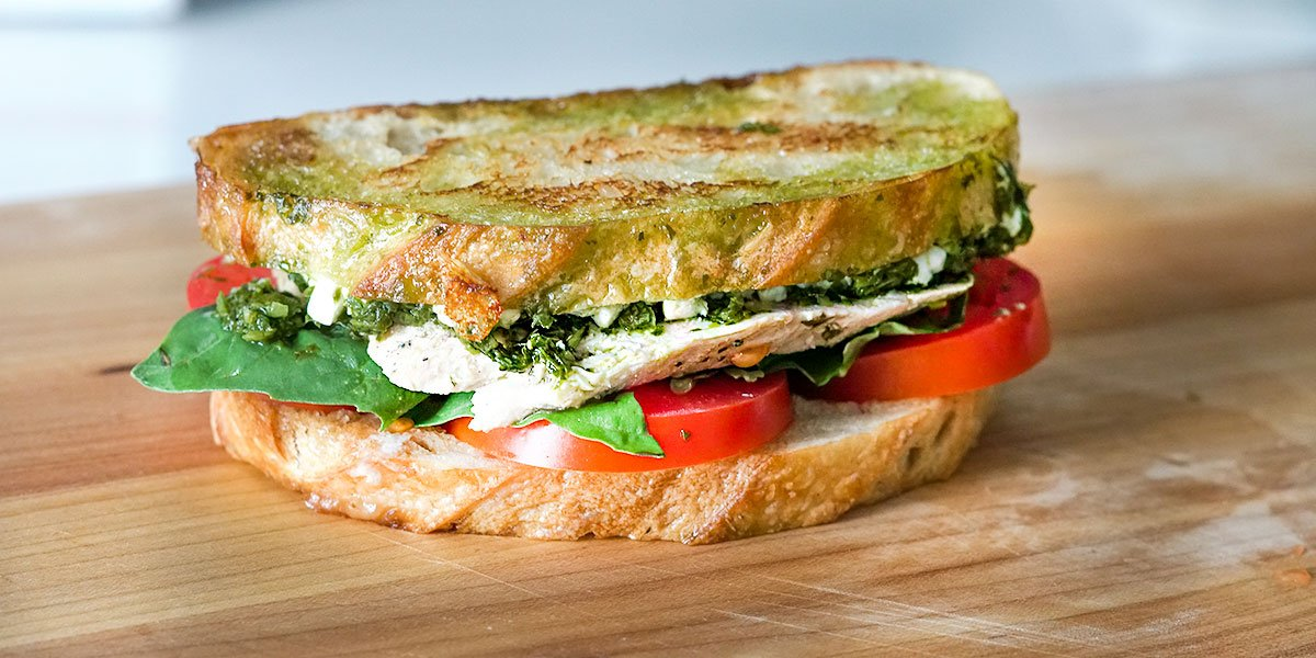Pesto Chicken Sandwich Recipe placed on top of a wood cutting board
