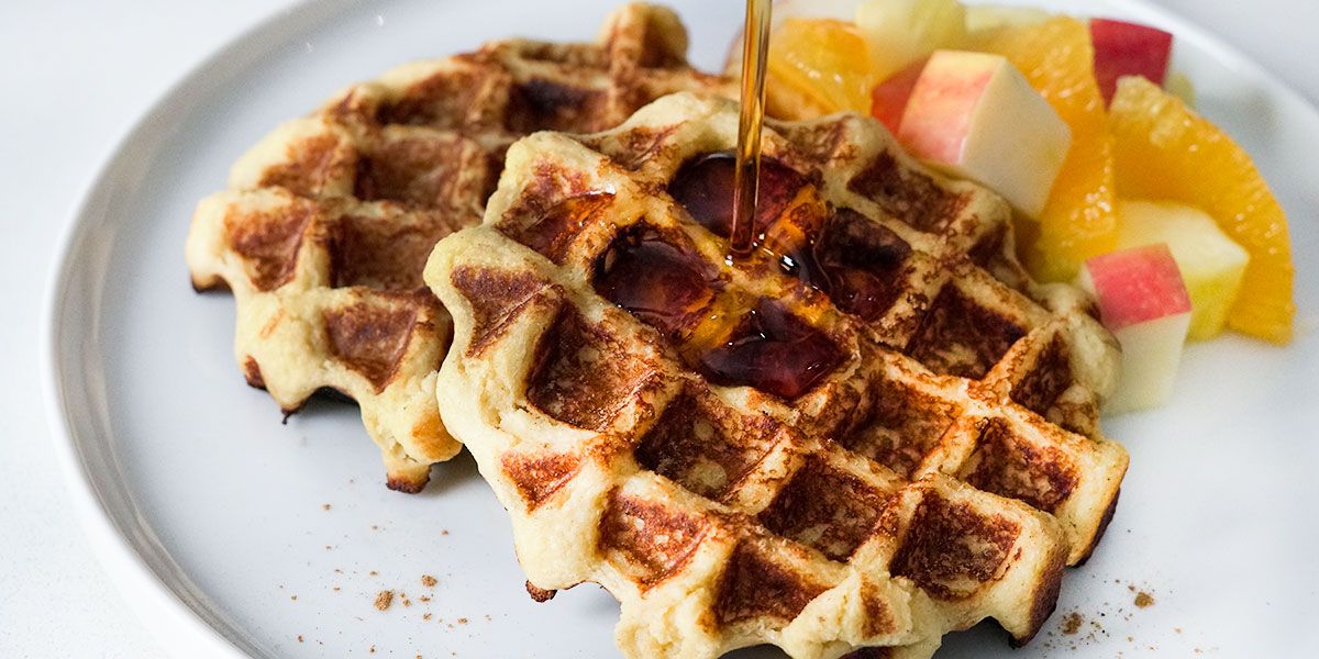 Maple Cinnamon Sweet Potato Waffle Recipe served with fruit on the side and syrup being poured on top