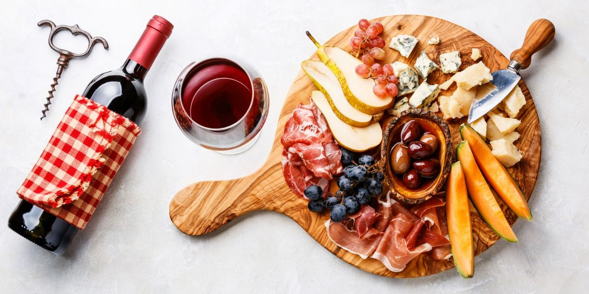 red-wine-glass-with-meat-cheese-and-fruit-platter