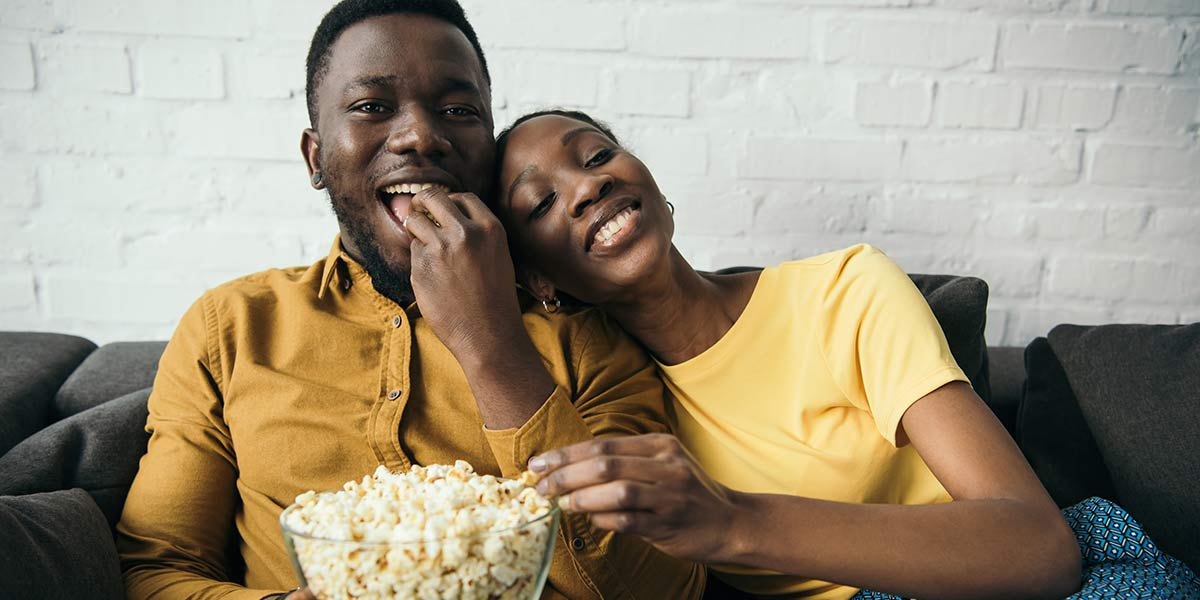 How to Stop Eating When Bored: 11 Tips for Avoid Boredom Eating: Young happy couple eating popcorn