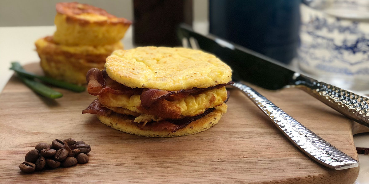 Keto Breakfast Sandwich Recipe on a board with utensils and egg bites in the background